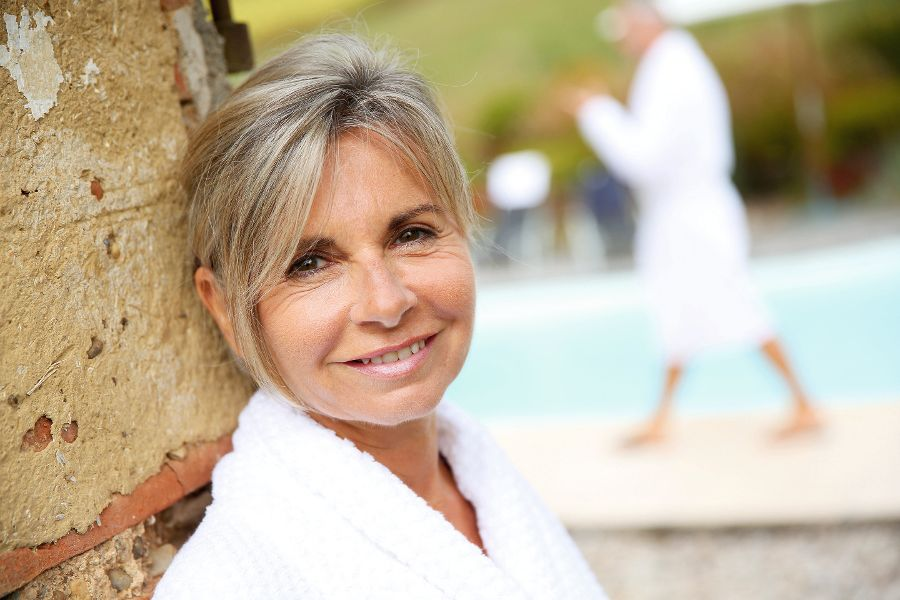 Portrait of smiling senior woman sitting by resort pool